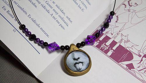 Gargantilla Saca la lengua Gargantilla de hilo de acero negro con camafeo de porcelana fría, cuentas de cristal y acrílico en negro y violeta e imagen dibujo esmaltada de una carita sacando la lengua.