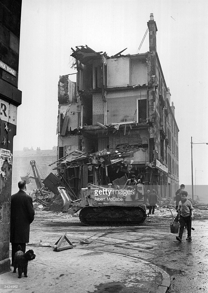 A workman in a bulldozer in front of a tenement being demolished in the Gorbals area of Glasgow The...
