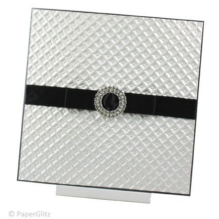 SOLITAIRE  A contemporary design with an exquisite embossed white pearl paper. It is finished off with a luxurious 15mm Black Double Sided Satin Ribbon and a round dual layer diamante buckle. The inside text is printed on Ice Gold card and the invitation comes with a matching envelope. Price: $7.95 https://www.facebook.com/NextChapterWeddingInvitations