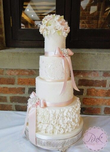 Wedding Cake with ruffles, pearls, piped dress detailing, and soft and pretty sugar florals