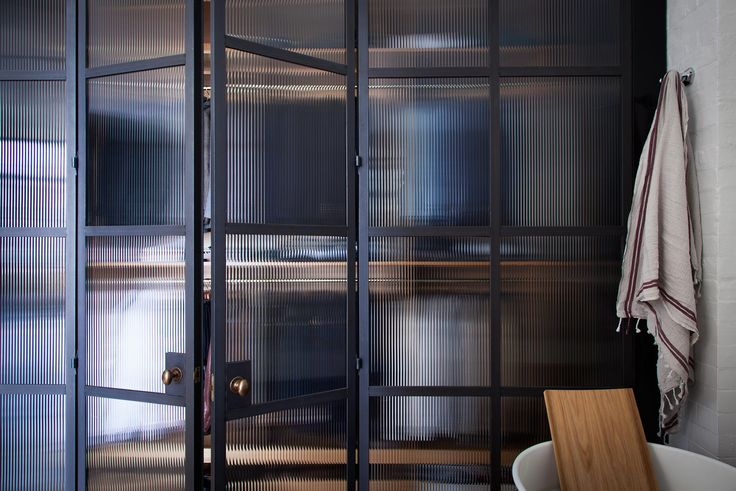 Bespoke Rolled Steel Glazed doors. Bathroom Screens with reeded fluted glass in the Old School House. Room divider.
