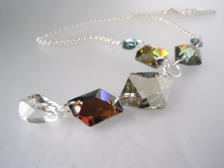 Halssmykket er satt sammen av Swarovski krystaller som er flate på baksiden. I tillegg er alle foliert med sølv folie slik at krystallene gnistrer og blinger så det suser!    Formene på krystallene er en mix av ulike former som gir en spennende effekt. Nederst henger en asymetrisk dråpe i sølskinnende krystall:)