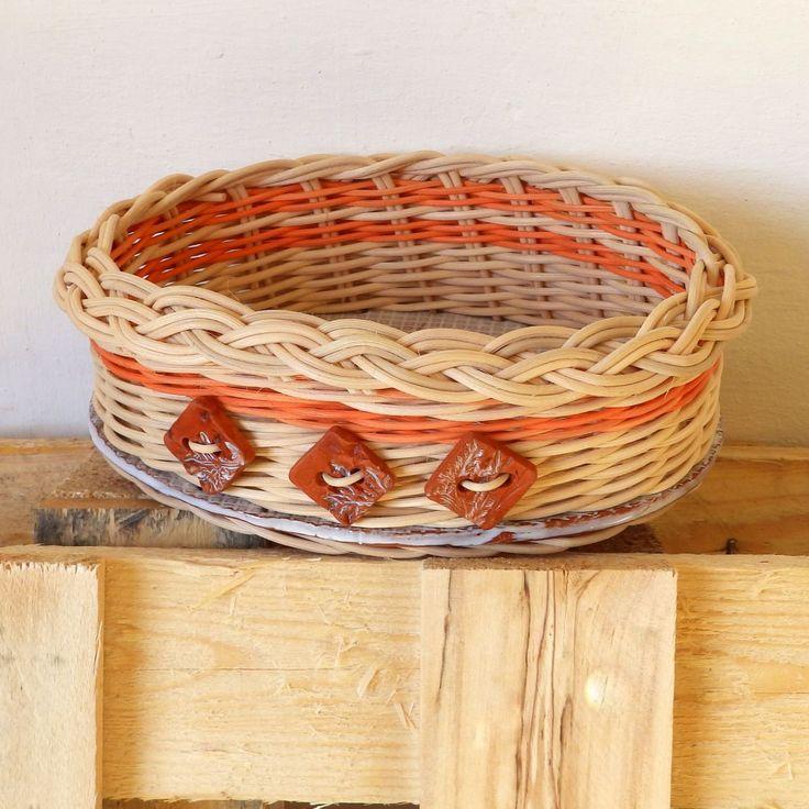 Košíček se třemi knoflíky Pěkný oválný košíček, pletený z přírodního a barevného pedigu, zdobený třemi ručně dělanými keramickými knoflíky.Dno je keramické,glazované, vypálené vysokou teplotou, podlepené oranžovým filcem.Rozměr dna je 15x21 cm, výškakošíčku je8 cm.
