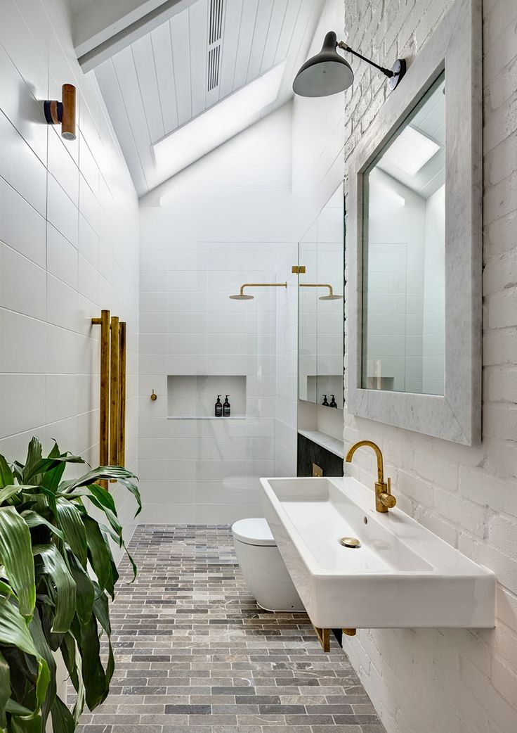 In this bathroom, white walls and ceilings make the brass accents and black…