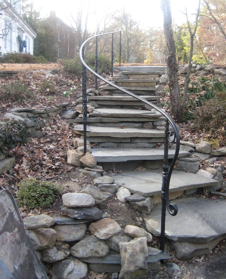 Decorative garden ironwork railing on stone steps with ornate posts and long lambs tongue termination by Appalachian Ironworks of Virginia.  Julin@appalachianironworks.com   http://appalachianironworks.com