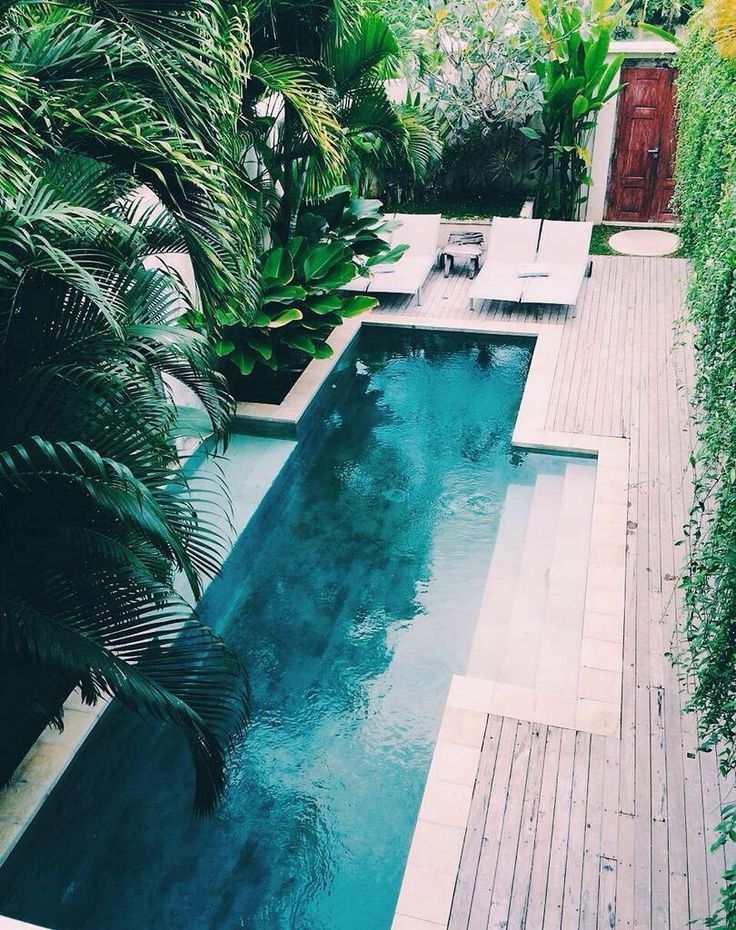 A Gorgeous Bali Themed Long Pool With Wood Decking And Tropical Plants.
