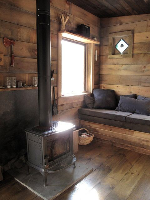 small cabin interior with wood stove and bench seat
