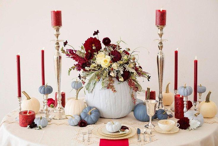 composition florale en vase-citrouille, begeoirs et bougies rouges