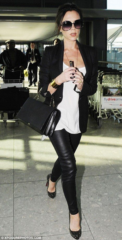 Any sign of a bump? Pregnant Victoria looked as slender as ever as she arrived at Heathrow Airport wearing a top, jeans, sunglasses and bag ...