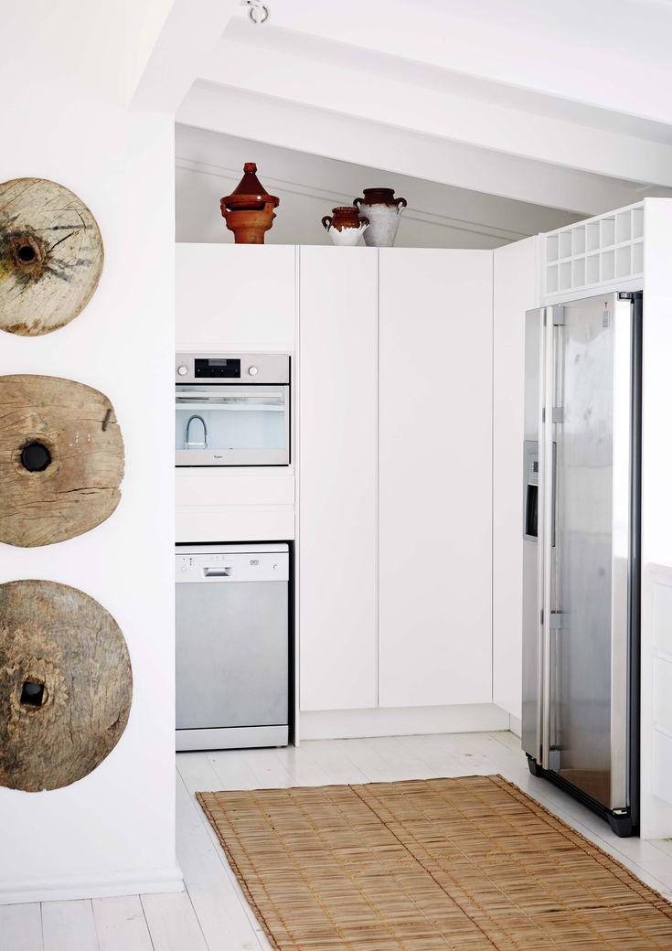 En la cocina de esta casa de fin de semana de Sudáfrica, los electrodomésticos engamados en acero están empotrados en un amplio mueble-alacena accesible pero no expuesto a la vista.