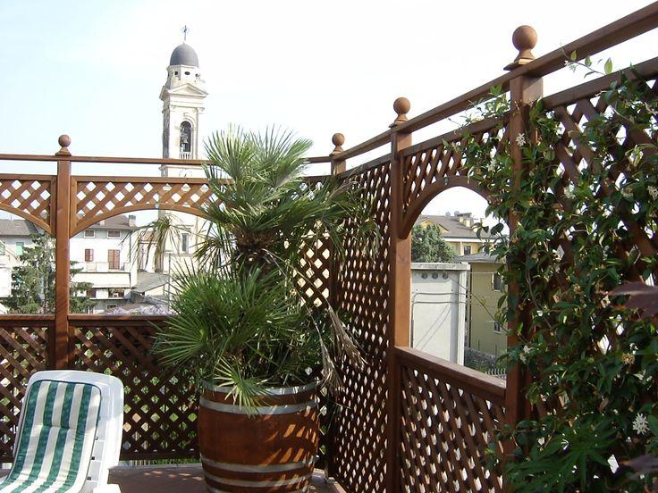 Arredo su terrazzo composto da pannelli grigliati e fioriere su misura con decorazioni. Legno impregnato a sali in autoclave + colore noce medio.