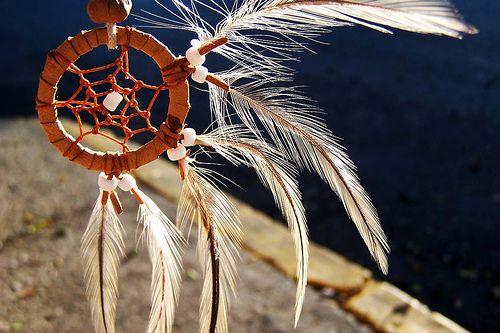 """El Atrapasueños es un objeto propio del pueblo Ojibwa, uno de los pueblos nativos de América del Norte, que tiene forma circular, tejido como una tela de araña con un orificio en medio y decorado con piedras y plumas. Para los Ojibwa, este objeto tiene propiedades mágicas de amuleto o talismán, conocido como """"cazador de sueños""""."""