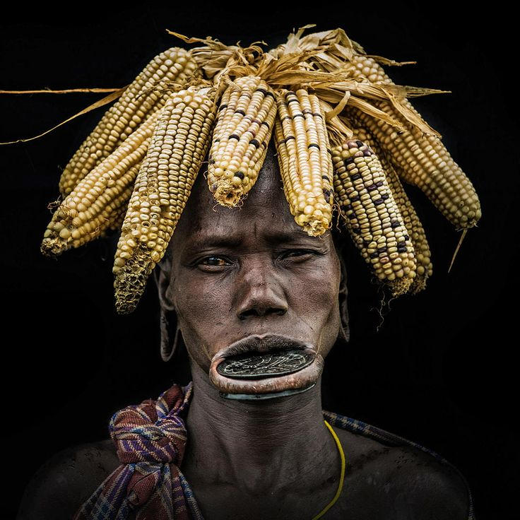 Corn cob headdress by Stefan Cruysberghs. The most famous tribe in Omo valley in southern Ethiopia is the Mursi. The women often wear a clay dish in their lower lip and all kind of special headdresses made of branches, cow horns, dried up fruits, animal skins, ...   The Mursi still live very traditional an livestock, mainly cattle, is their most valued possession and also a measure of social status...