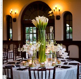 The bride wanted everything to be a mix of modern and traditional. Tight grouping of calla lilies shot out of tall glass vases, which were surrounded by smaller vases of phalaenopsis and dendrobium orchids.