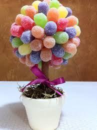 Árvores de bala de goma -Para que as flores não fiquem sozinhas na mesa, você pode fazer uma árvore utilizando balas de goma.  Materiais  1 palito de churrasco  1 bola de isopor  Palitos de dente  1 vaso de madeira ou vidro  Pedaço de isopor para encaixar no vaso escolhido  Papel crepom  Balas de goma