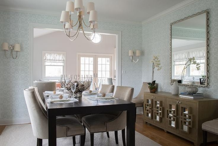 Blue and brown dining room features a Reed Eight Light Chandelier illuminating a dark brown dining table lined with beige nailhead dining chairs.