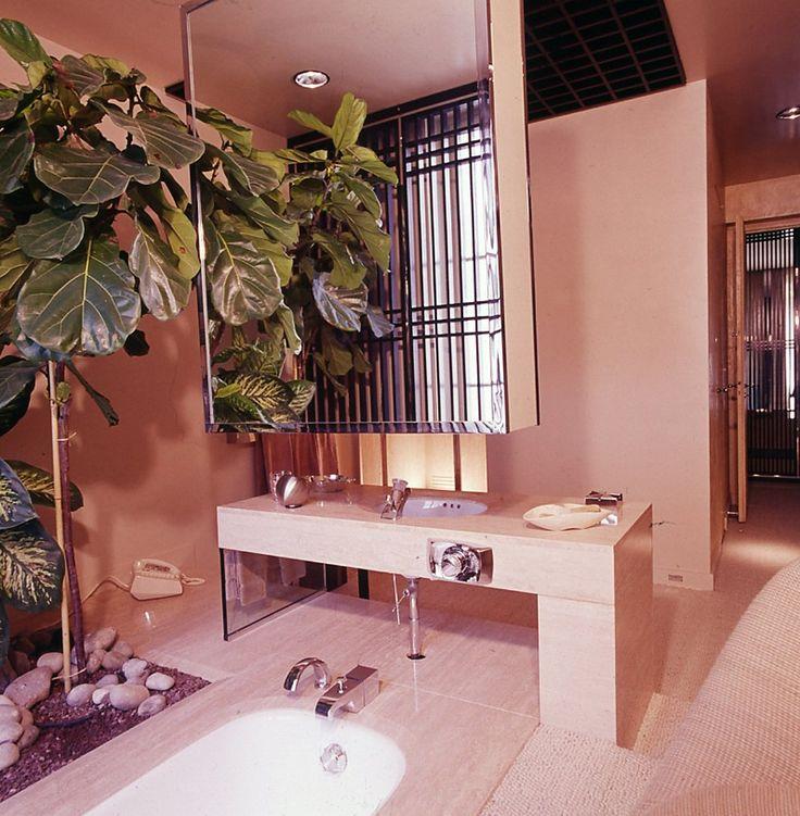 francois catroux 1975 floating medicine chest art deco interior designer bathroom faux plants palm tree decor pink pastel rose quartz modern powder room master bath shop room ideas retro