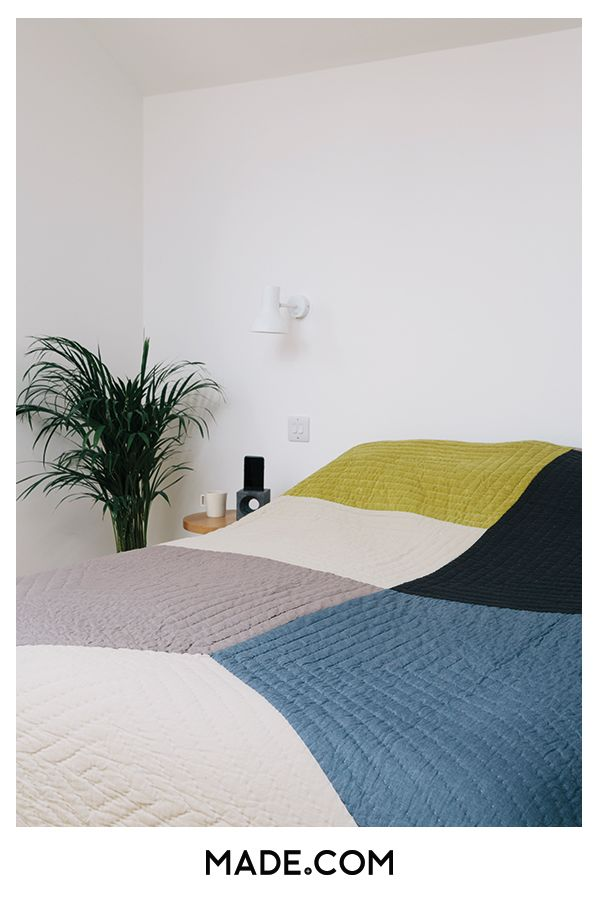 White walls in a bedroom can be brought to life with a multicoloured throw and some leafy plants