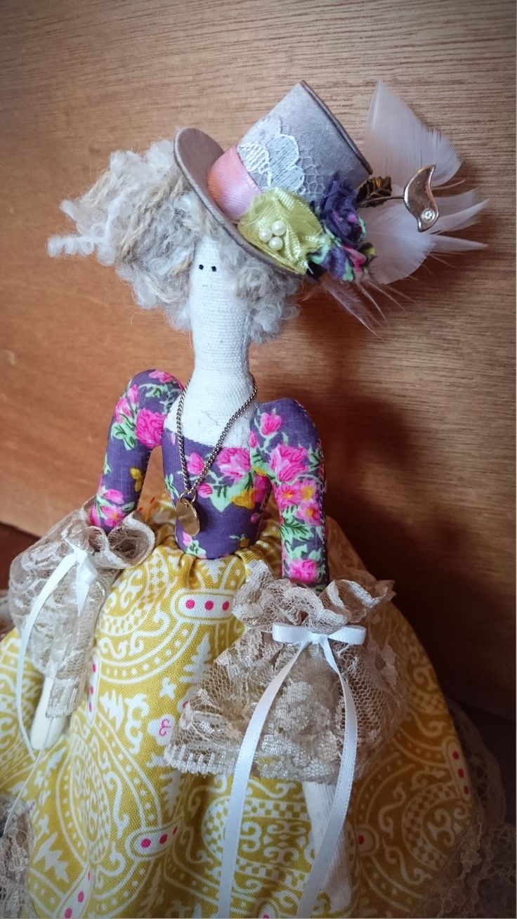 - Tilda Doll (close-up) - Dressed in a long skirt decorated with lace and pearls. The doll is also embellished with a golden necklace and a top hat with feathers.
