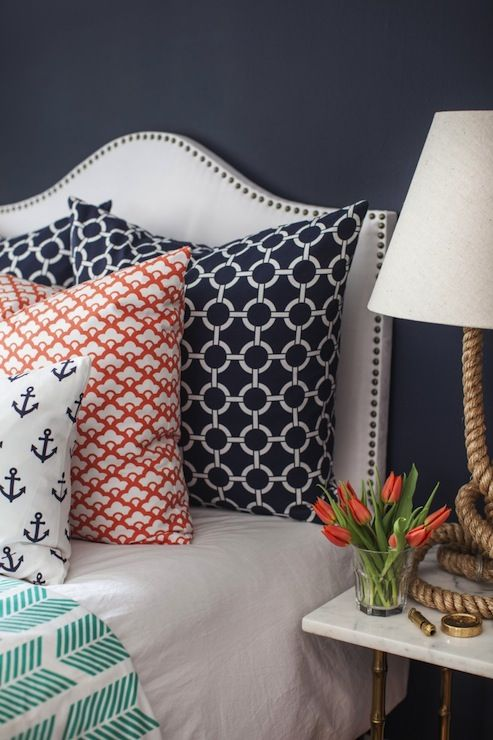 Caitlin Wilson Textiles | navy walls and a white upholstered headboard with nailhead trim | Navy Links Pillows | red and ivory geometric pillows | Navy Anchors Away Pillow | Teal Arrows Blanket | white bed linen | Gold faux bamboo marble topped nightstand | Serena and Lily Spinnaker Lamp