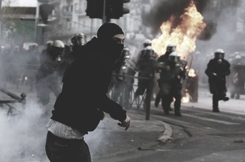 Traitors rush to stop a survivor rebel from throwing a fire grenade.