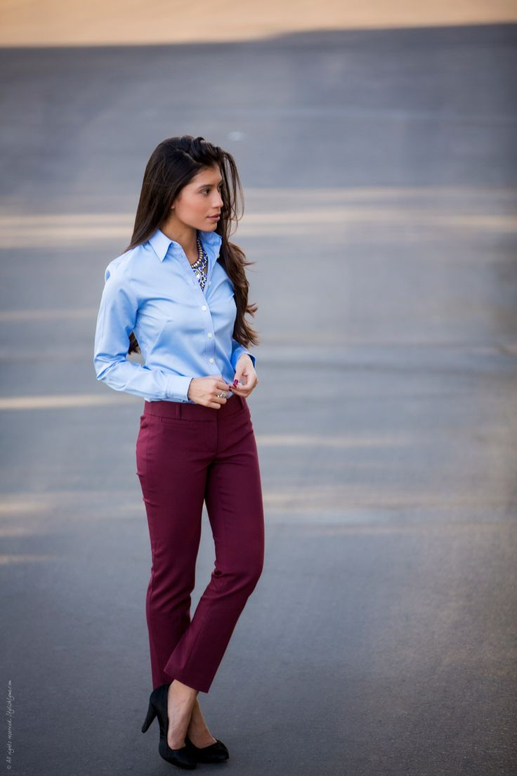 Button down collared shirt with deep purple skinny pant and pumps. She just needs a great blazer - Black for formal or a khaki for casual.