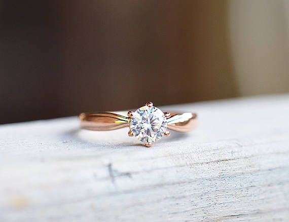 This ring features a Swiss round cut, 0.8 carat solitaire CZ diamond set in a 18k rose gold overlaid band. The rose gold is pressure bonded to the base metal 5 times over, and is not quick to fade. This sparkling keepsake mimics the luminescence of natural diamonds without the hefty price and ethical conflict of the current diamond trade.  Jewellery Specifications:  Metal: 18k rose gold over stainless steel Gemstone: 0.8ct hand cut cubic zirconia Stone dimensions: 4 x 4mm Colour: Rich rose…
