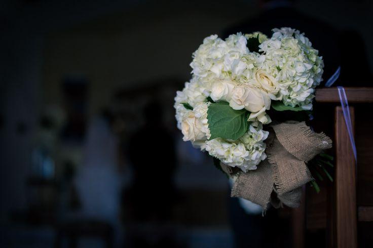 Ramos de hortensias y rosas blancas, amarrados con lazos de tela de yute en los bancos de una iglesia muy campestre.