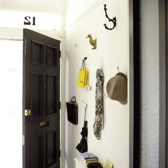 Instead a coat rack, put up an assortment of coat hooks. We love this whimsical mix of vintage coat hooks with the run-of-the-mill kind to make this entryway unique even when its not covered in coats and jackets.