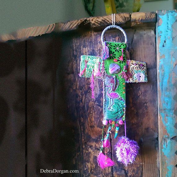 Deze kunstzinnige muur opknoping van een kruis is de eerste van zes, dat eindelijk kreeg klaar!... en bestaat meestal vintage textiel met sommige beading, raggedy pom pom, hete roze veer, hand geschilderd tusk, een plakje roze Agaat, een Paua shell tusk en sommige kleine handgemaakte tassles. Het wordt ondersteund met een zachte velveteen type stof, in fuchsia roze. Het hangt van een Lila gekleurde raffia ring.  Het heeft veel detail en hand stiksel en zorgt voor een zoete, kitscherige…