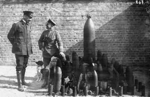 WWI, German marine officers and their dog by a collection of unexploded shells in Flanders. ©IWM  (Q 87585)