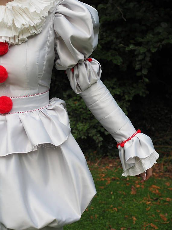 Youll Float too.... in this Pennywise dress with pants. Perfect for Halloween or cosplay! Can me made to mens or womens measurements. Fitted bodice with pleats and red pom pom detail. Pleated skirts with tulip effect. Linen neck ruff and cuff lining. Long mutton sleeves with red