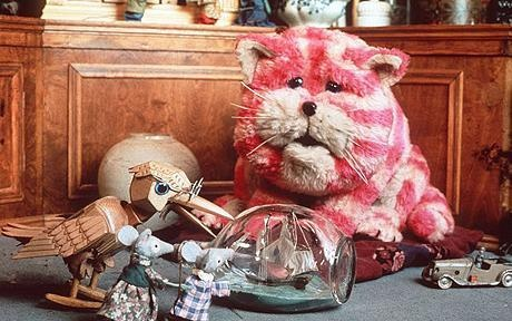 Once upon a time, not so long ago, there was a little girl and her name was Emily, and she had a shop. There it is! It was rather an unusual shop because it didn't sell anything. You see, everything in that shop window was a thing that somebody had once lost and Emily had found and brought home to Bagpuss. Emily's cat Bagpuss. The most important, the most beautiful, the most magical, saggy old cloth cat in the whole wide world.