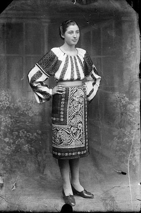A woman in traditional dress poses for a portrait 30s found photo print street ethnic boho peasant embroidered blouse skirt vintage fashion