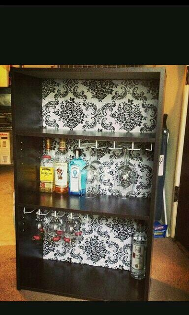 Homemade liquor cabinet made from a book shelf! I need to do this. Find a cheap IKEA bookshelf and paint the inside. Maybe glue some pictures on the inside of all my friends?