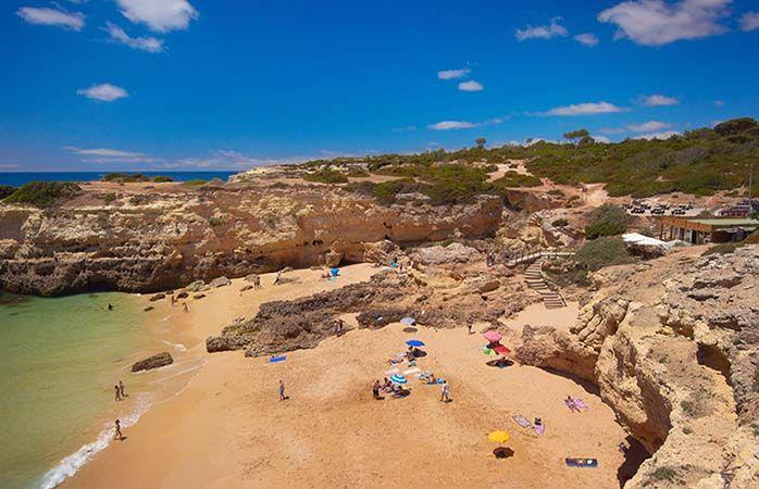 Praia do Albandeira, Armacao de Pera, Algarve, Portugal. A Praia de Albandeira é uma praia situada na zona de Caramujeira, e conhecida pelas suas águas cristalinas quase paradisíacas. Estas piscinas naturais, divididas ao meio por uma massa rochosa, são muito tranquilas e pouco frequentadas, contribuindo para umas férias cheias de paz e serenidade. O acesso mais difícil pode ser uma das razões pelas quais esta praia é quase deserta: é  percorrer uma estrada estreita até  ao bendito paraíso.