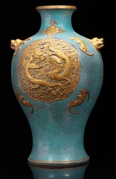 CHINE  Vase de forme balustre en trompe l'oeil à l'imitation du bronze; il est décoré sur la panse en léger relief de deux dragons dorés dans des réserves sur fond de nuages entourés de quatre chauve souris et d'une fleur de lotus, sur fond bleu à décor incisé de fleurs, les deux anses simulant des têtes de chimères. Au revers marque moulée qianlong en zhuanshu rehaussée de dorure. XIXème siècle. H: 32 cm. Le col monté en lampe