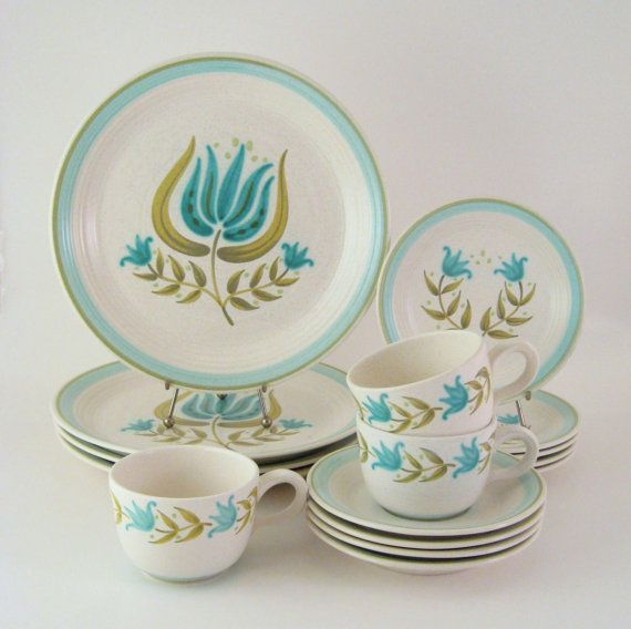 """Vintage dinnerware set produced by Franciscan China for their Earthenware line. The pattern was named """"Tulip Time"""" and was in production from 1963 to 1973. The design features large stylized tulips in blue and avocado green, set on a pretty off-white base with light brown flecks. The earthenware plates have a subtle ribbed texture with bands of blue and green along the rim."""