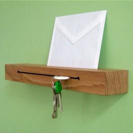 Schlüsselbrett aus Eichenholz    Produkt-Informationen    Das Schlüsselbrett neben der Tür im Flur schützt vor Verlegen und Vergessen. Gleichzeitig dient die zierliche Ablage zum Platzieren der aktuellen Post in der Nähe der Garderobe. Das ist praktisch und sieht zeitgleich gut aus.  Die Schlüssel werden in die Halterung gesteckt. Sie verkanten sich in dem Schlitz und dadurch halten darin ganze Schlüsselbunde.  Etwas sperrigere Autoschlüssel passen evt in die Rundlöcher, durch welche das…