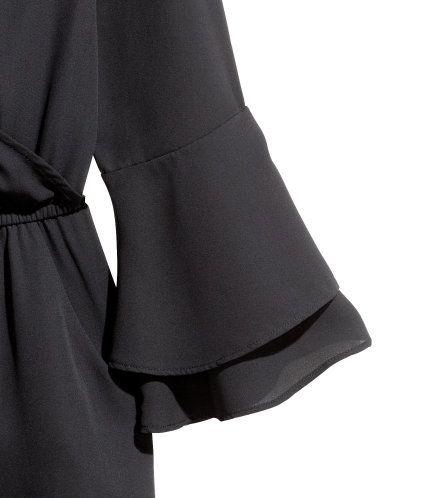 Schwarz. Jumpsuit aus zartem Kreppstoff. Der Jumpsuit hat einen V-Ausschnitt im Wickelschnitt, 3/4-lange Trompetenärmel und einen tiefen, geknöpften