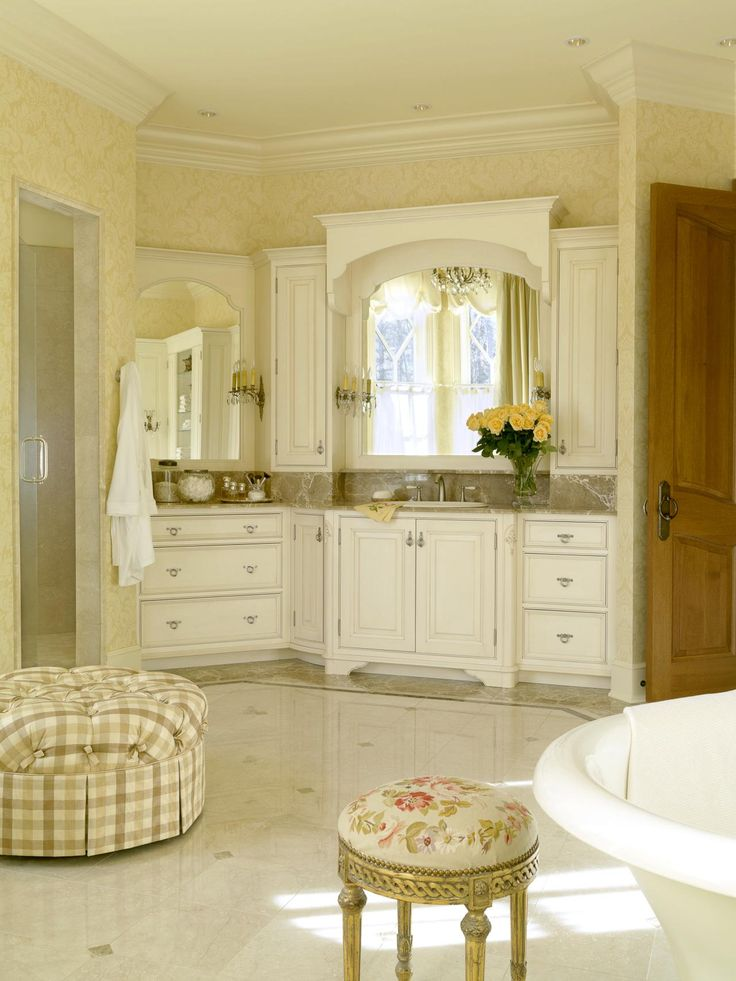 Stylish bathroom in French country style with white cabinets on travertine floor  #travertine #floor #bathroom #interior #naturalstone