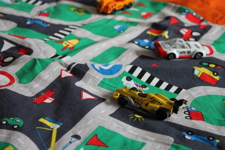 """Petite création pour les enfants fans de petites voitures ! Un tapis """"route"""", rond pour y faire évoluer les véhicules en tous genre ! Vite il faut ranger ? On tire sur la ficelle au dos et voilà, un baluchon avec les voitures dedans ! Blandine"""