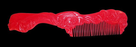 Probablymade in the United States, this red plastic comb dates from 1950-1980 and incorporates thefun design of a female head symbolizingthe north wind as the handle with flowing hair making up the body of the comb. A charming addition to any vintage display.  Circa: 1950-1980  Condition: Excellent Flaws: None Size: 8 13/16 long, 2 wide  Designer: Unmarked