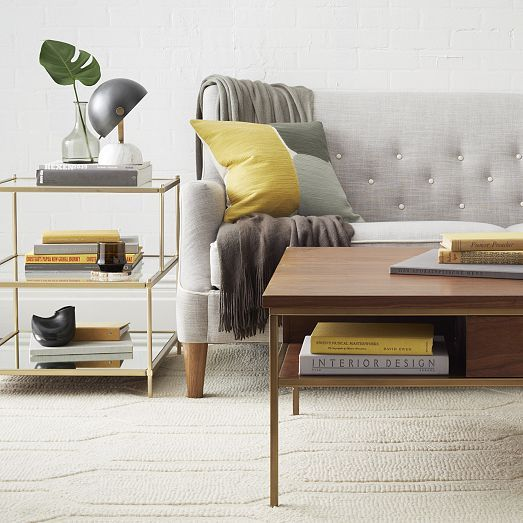 Inspired by mid-century design, the Terrace Side Table's antique brass finish gives it a pretty patina, while tiered clear glass shelves appear to float above a mirrored glass base. With its refined silhouette, it's perfect for placing on either end of a sofa or beside a bed.