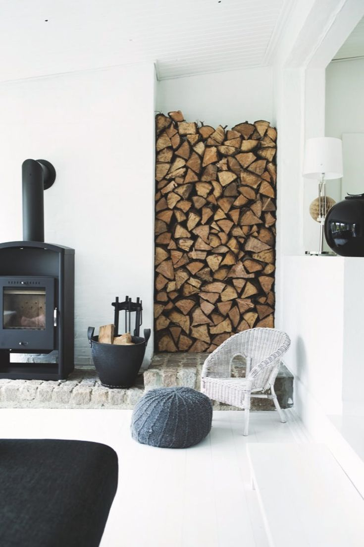 Simple fireplace with modern surroundings - the woodpile-niche is a cool detail and together with the simple decor it creates a perfect Scandinavian look.