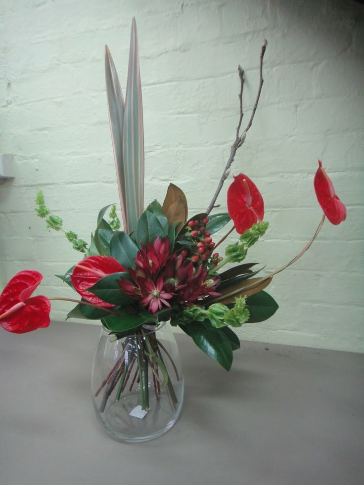 Formal Linear - Materials used: anthirium, bells of ireland, ruscus, and branches. This design moves your eye from left to right and brings the color to the sides of the design. This can be used as a centerpiece or a gift