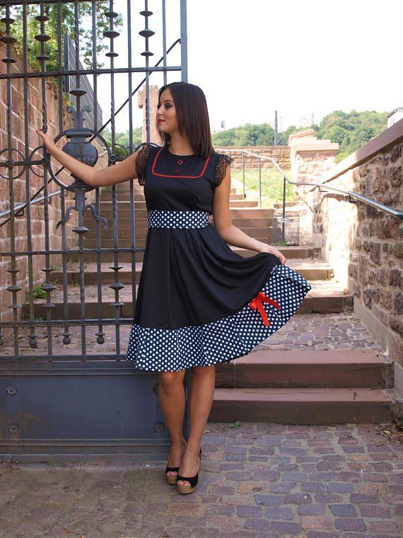 Schwarzes Stretch Kleid, Rockabilly, Pinup Kleid. Das Kleid hat einen weit schwingenden Rock, Tellerrock und kann auch mit einem Petticoat getragen werden. Die Borte unten und der Gürtel zum binden, sind aus Baumwolle in Navy Blau mit weißen Punkten. Das Kleid hat schwarze Ärmel aus