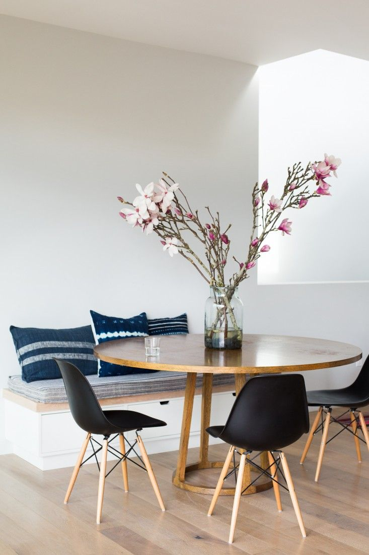 Blue and white vintage hemp cushions and black Eames Molded Plastic Side Chairs with a Wood Dowel Base