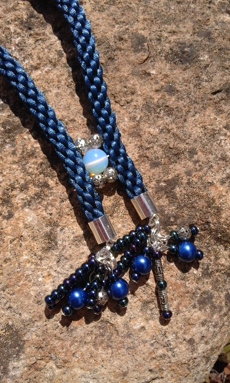 Royal blue kumihimo braids, and similar cloured beads beside silver ones.