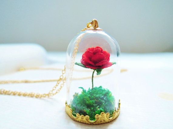 Inside the glass tube sealed with a gold plated metal lid, there is a red flannelet rose on a grassland. You could see the rose blossoms very beautifully though the glass